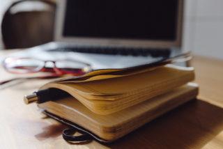 escritorio con una agenda apuntes computadora