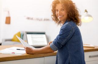mujer sonriente con ordenador portatil y papeles en las manos