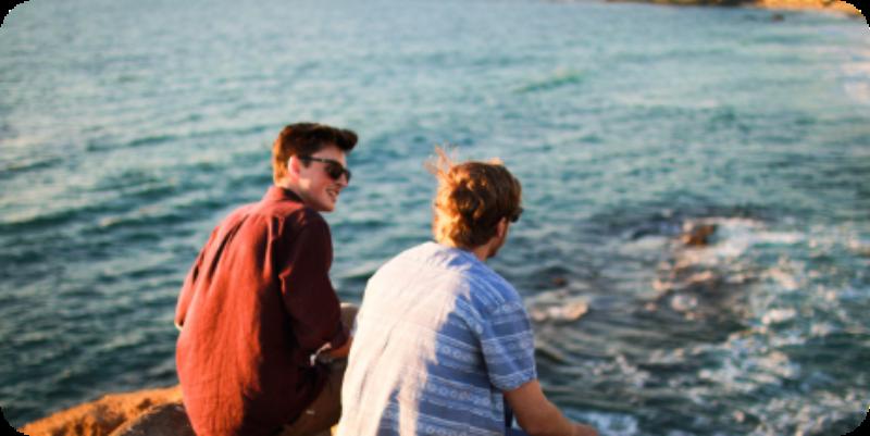 dos chicos cerca del mar en una roca