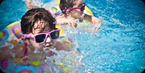 niñas en la piscina con flotador y gafas de sol