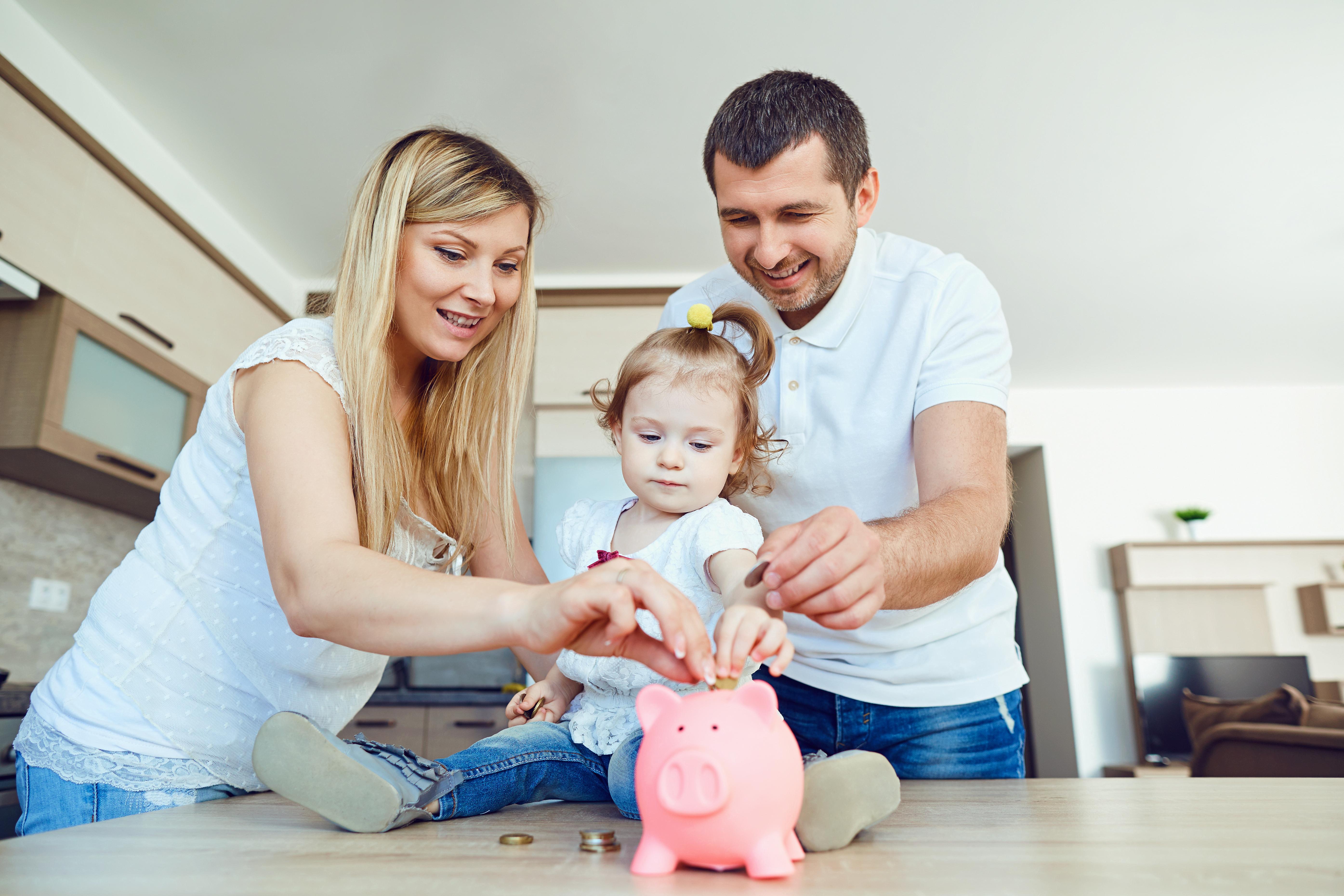 pareja joven con un bebe metiendo dinero en una hucha de cerdito